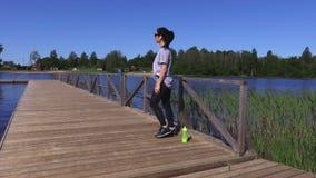 Die Frau, die Übung für Beine tut, nähern sich See im Sommer stock video