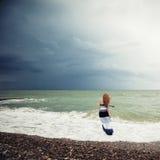 Die Frau auf dem Strand während eines Sturms Stockfotos