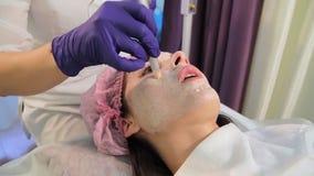 Die Frau auf dem Verfahren des Erleichterns der Haut Das geduldige ` s Gesicht in der Nahaufnahme Das Gerät dermapen orientalisch stock video