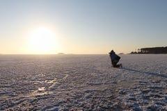 Die Frau auf den Rochen, die einen Sonnenuntergang auf dem Fluss schießen Stockbilder