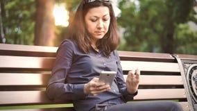Die Frau, die auf der Bank sitzt, leistet Online-Zahlungen stock footage