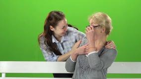 Die Frau, die auf einer Bank von hinten sitzt, kommt Tochter und macht eine Überraschung Grüner Bildschirm Langsame Bewegung stock video