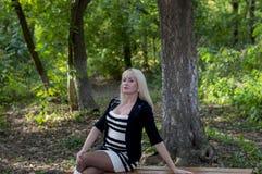 Die Frau auf einer Bank vor dem hintergrund des Holzes Lizenzfreie Stockfotografie
