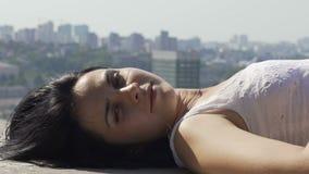 Die Frau, die auf Rand der Dachspitze liegt, dreht den lächelnden Kopf, schönes entspanntes weibliches Gesicht stock footage
