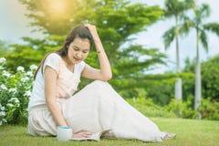 Die Frau, die auf Rasenfläche im Allgemeinen Garten für morgens lesen sitzt, entspannen sich Zeit der asiatischen Frau lizenzfreie stockfotos