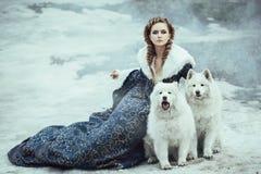 Die Frau auf Winterweg mit einem Hund Lizenzfreie Stockfotos