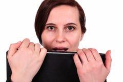 Die Frau beißt den Ordner mit Dokumenten Lizenzfreie Stockfotografie