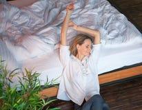 Die Frau, die in Bett nach ausdehnt, wachen auf stockbild