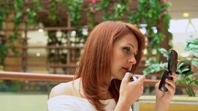 Die Frau bildet Lippen im Einkaufszentrum Die junge Frau schaut in einem Taschenspiegel und bildet Lippen im Geschäftsmall stock video footage