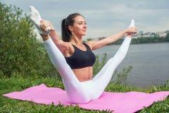 Die Frau, die das getrennthandeln der Beine hält, übt Aerobic aus, die mit Gymnastik für das Flexibilitätsbein aufwärmt, das Trai Stockfotos
