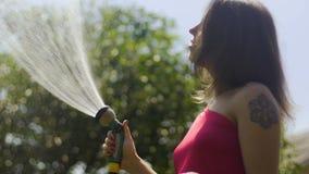 Die Frau, die das Gras im Garten lächelnd wässert, Frau genießt, Zeitlupe zu wässern stock footage