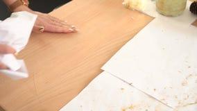 Die Frau, die das Haus säubert, wischt Staub und Funkeln von der Tabelle mit einem Papier ab Hausarbeiten stock video footage