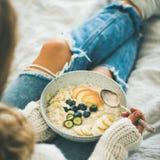 Die Frau in den Jeans und die Strickjacke, die strengen Vegetarier essen, frühstücken, quadratische Ernte lizenzfreie stockfotos