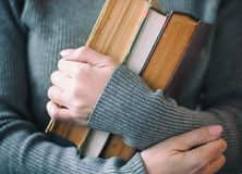 Die Frau in der grauen Kleidung hält drei Bücher in der Hand stockfotos