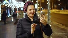 Die Frau in der lebhaften Nachtzeit von Tageswachen etwas nett, das ihr Beharren im telefon anhob stock video footage