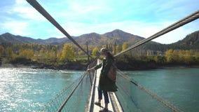 Die Frau der Reisende geht der Priester zur Hängebrücke des Gebirgsflusses Berg Altai stock footage