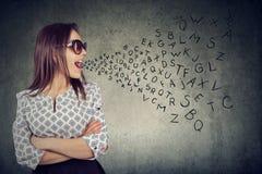 Die Frau in der Sonnenbrille sprechend mit Alphabet beschriftet das Herauskommen aus ihren Mund stockbilder