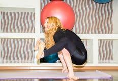 Die Frau, die Übungsyoga tun und die pilates werfen auf Matte in der Turnhalle auf Asana Das Konzept des Sports, der Eignung, des Stockfotos