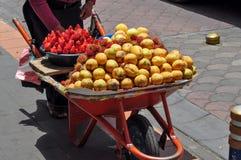 Die Frau, die Achiote verkauft, trägt in den Straßen von Otavalo, Ecuador Früchte Stockfotos
