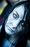Die Frau, die als Zombie gekleidet wird, führt auf eine Straße während eines Zombiewegs vor Lizenzfreies Stockbild