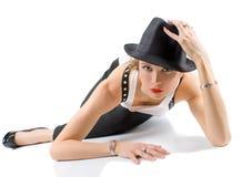Die Frau, die auf dem Fußboden liegt und halten Ihren schwarzen Hut an Stockbild