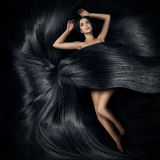 Die Frau, die auf dem Haar liegt und umfassen ihre Karosserie lizenzfreie stockfotografie