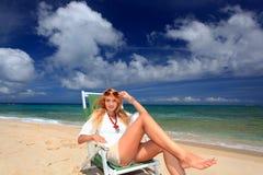 Die Frau, die auf dem Strand sich entspannt. Lizenzfreie Stockbilder