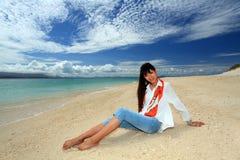 Die Frau, die auf dem Strand sich entspannt. Stockbilder