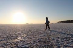 Die Frau, die auf den gefrorenen Fluss bei Sonnenuntergang eisläuft Stockbilder