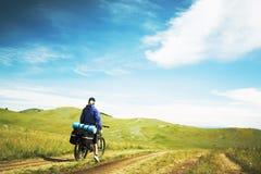 Die Frau, die auf ein Fahrrad geht Stockfoto