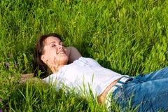 Die Frau, die auf einen Rasen legt und träumt Lizenzfreie Stockfotografie
