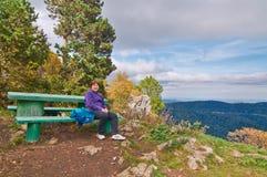 Die Frau, die auf einer grünen Bank an der Gebirgsspitze sitzt Stockfotos