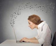 Die Frau, die auf ihrer Laptop-Computer mit Alphabet schreibt, beschriftet Fliegen Stockbild