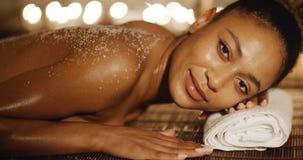 Die Frau, die auf Massage-Tabelle mit Salz liegt, scheuern sich Stockfoto