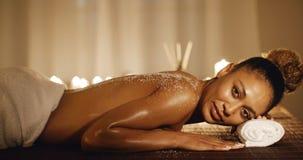 Die Frau, die auf Massage-Tabelle mit Salz liegt, scheuern sich Lizenzfreies Stockbild