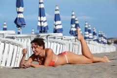 Die Frau, die auf Sand liegt und nehmen auf Strand ein Sonnenbad Stockbilder