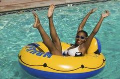 Die Frau, die auf Schlauchboot im Swimmingpool mit den Armen und den Beinen liegt, hob Porträt an. Lizenzfreie Stockfotos