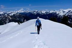 Die Frau, die auf Schnee geht, umfasste Gebirgsspitze mit schönen Ansichten Stockfotografie