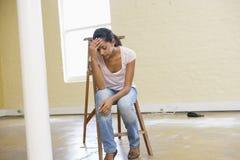 Die Frau, die auf Strichleiter im leeren Platz sitzt, schaut müde Lizenzfreie Stockfotografie