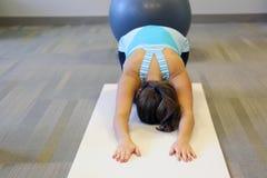 Die Frau, die childs tut, werfen in der Yogaklasse im Eignungsstudio auf Lizenzfreie Stockbilder