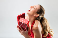 Die Frau, die das Geschenk öffnet und ist glücklich Lizenzfreie Stockfotografie