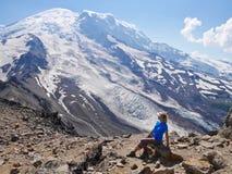 Die Frau, die an den Felsen mit Eis sitzt, umfasste Bergblick Stockbilder