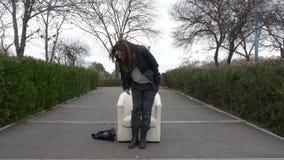 Die Frau, die in den Park geht, findet einen Lehnsessel auf einer Gasse und Reste in ihr - VR stock video footage