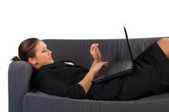 Die Frau, die der Geschäftsmann auf einem Sofa niedergelegt hat lizenzfreies stockfoto