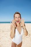 Die Frau, die durch Megaphon schreit, formte Hände am sandigen Strand Lizenzfreies Stockfoto