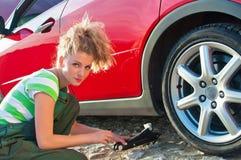 Die Frau, die ein Auto repariert, schrauben das Rad ab Lizenzfreies Stockfoto