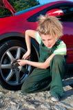 Die Frau, die ein Auto repariert, schrauben das Rad ab Lizenzfreies Stockbild