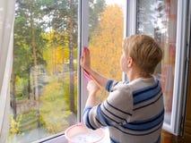 Die Frau, die ein Fenster wäscht. Stockfotografie