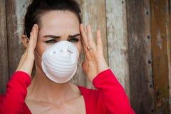 Die Frau, die eine Gesichtsmaske trägt, hat Kopfschmerzen Stockbilder