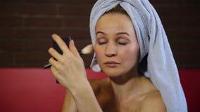 Die Frau, die in einem Badtuch gekleidet wird, macht ein Make-up und wendet Farben an, erröten auf Backe Zutreffen des transparen stock video footage
